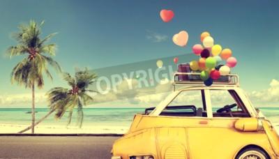 Quadro Automobile gialla d'annata con il pallone variopinto del cuore sul cielo blu della spiaggia - concetto di amore in estate e nozze. Viaggio di nozze