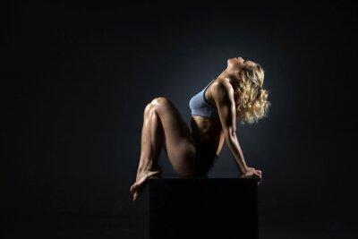 Quadro Bella giovane donna in forma con corpo muscoloso sottile in abbigliamento sportivo facendo esercizio sportivo. Full length, vista laterale, girato in studio, sfondo nero.
