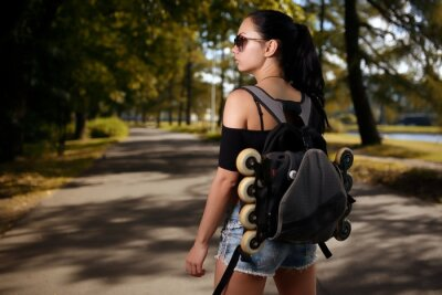 Quadro Bella ragazza bruna con zaino alle spalle in quali pattini a rotelle