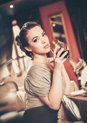Quadro Bella ragazza con un bicchiere di rosso winein un ristorante