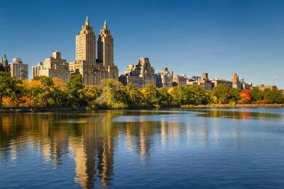 Quadro Central Park e Manhattan, Upper West Side, con caduta foglie colorate. Un cielo azzurro e gli edifici di Central Park West, riflettendo in Jacqueline Kennedy Onassis Reservoir. New York City.