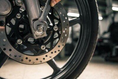 Quadro Chiuda in su della chiave di montaggio della holding della mano dell'uomo vicino al veicolo del motociclo.