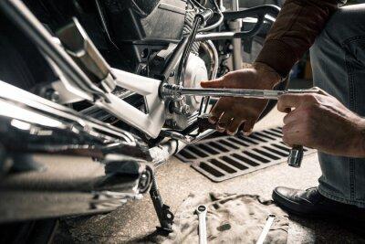 Quadro Chiuda in su delle mani dell'uomo con il motociclo nel garage
