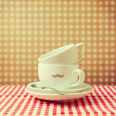 Quadro Coffee cups with hipster  mustache on checked tablecloth