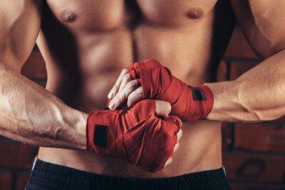 Quadro Combattente muscolare con Red Bende sullo sfondo di un muro di mattoni