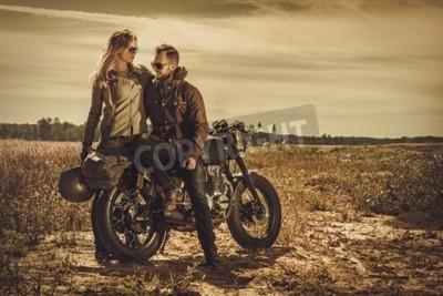 Quadro Coppie giovani, alla moda del corridore del caffè sui motocicli su ordinazione dell'annata in un campo.