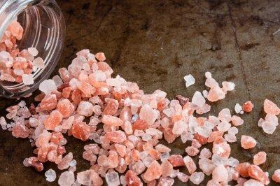 Quadro cristalli di sale rosa dell'Himalaya sparse dalla bottiglia di vetro su sfondo metallo arrugginito