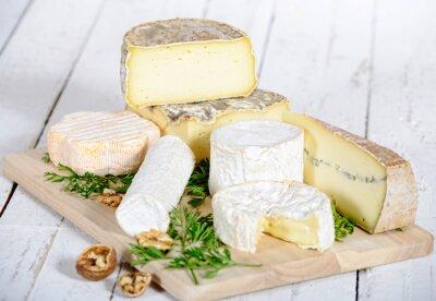 Quadro diversi formaggi con noci su una tavola di legno bianco