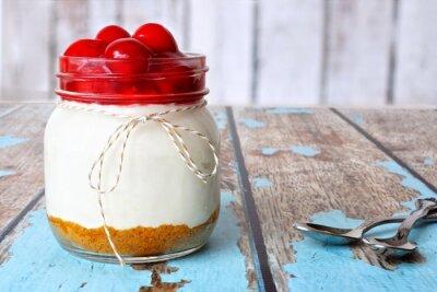 Quadro Dolce cheesecake ciliegia in un vaso di muratore su uno sfondo di legno rustico