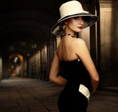 Quadro Donna in abito nero e grande cappello bianco solo all'aperto di notte