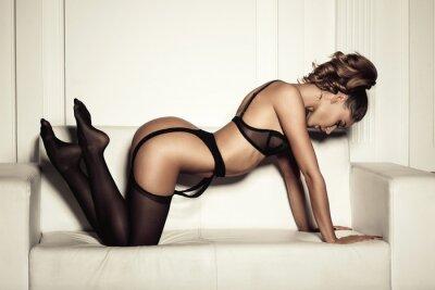 Quadro donna sexy in lingerie nera seducente seduto su un divano in sto