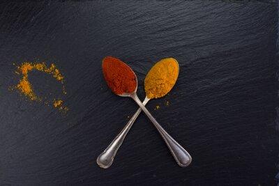 Quadro Due cucchiai d'epoca con spezie curry e paprika su sfondo nero.