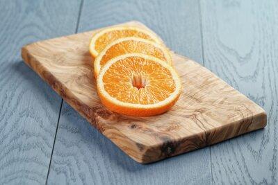 Quadro fette di arancia maturi sul tagliere di oliva, fuoco poco profondo