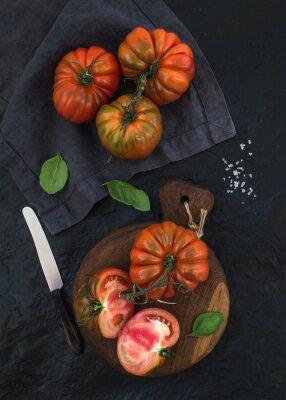 Quadro Freschi pomodori maturi hairloom e foglie di basilico su tavola di legno rustico su sfondo nero pietra.