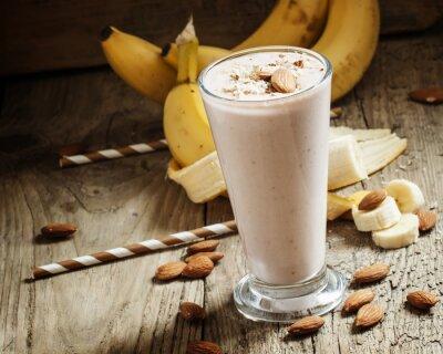 Quadro frullato di banana con latte, mandorle tritate in una grande tazza sul