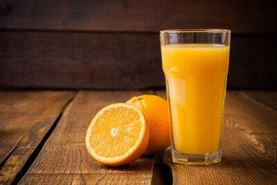 Quadro Frutta arancione e bicchiere di succo su sfondo marrone di legno