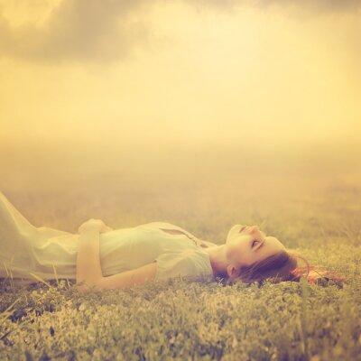 Quadro giovane e bella ragazza sogna di sdraiato su un prato magico in primavera