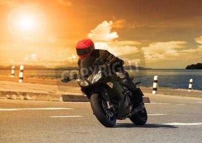 Quadro giovane in sella grande moto bicicletta contro tagliente curva di asfalto strada maestra modi con l'utilizzo lago scena rurale per le attività di avventura di sesso maschile e sport motoristici mio ho