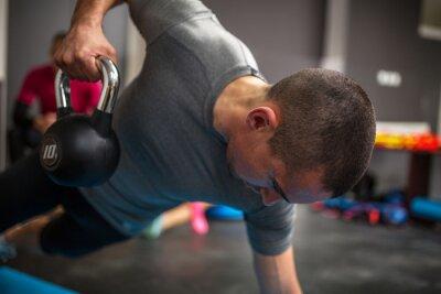 Quadro Giovane manubrio di sollevamento uomo e kettlebell presso il centro fitness