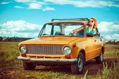 Quadro La donna è alla guida di una vecchia auto gialla. Rurali di fondo.