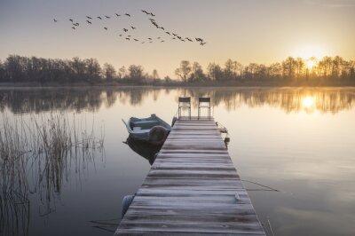 Quadro łódka zacumowana zimą do drewnianego pomostu