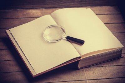 Quadro Loupa e libro sul tavolo in legno