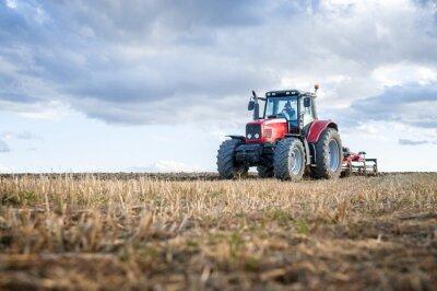 Quadro Macchine agricole in primo piano che svolgono lavori in campo.