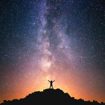 Quadro Man and the Universe. A person is standing on the top of the hill next to the Milky Way galaxy with his hands raised to the air.