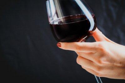 Quadro Mano che regge un bicchiere di vino rosso su sfondo grigio scuro