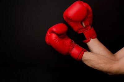 Quadro Mano in guanti da boxe rossi in un angolo della cornice su uno sfondo nero, lo spazio vuoto