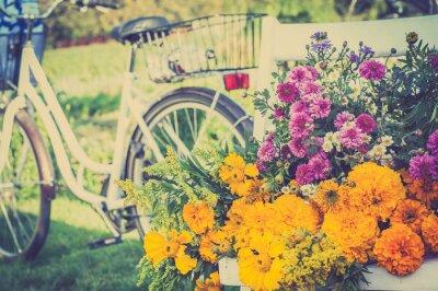 Quadro Mazzo di fiori su una sedia bianca. Offuscata retrò bicicletta in background.