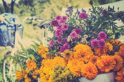Quadro Mazzo di fiori su una sedia bianca. Offuscata retrò bicicletta nel bac