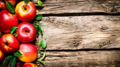 Quadro mele rosse fresche con foglie verdi su tavola di legno.