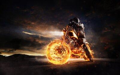 Quadro Motociclista scuro che rimane sulla motocicletta bruciante nella luce del tramonto