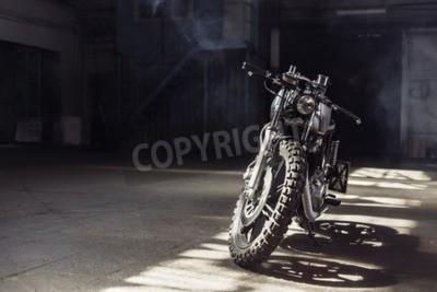 Quadro Motociclo d'annata che si leva in piedi in una costruzione scura nei raggi di luce solare. Colori tinti Vista frontale