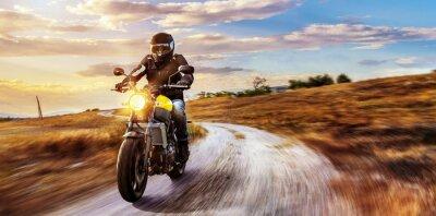 Quadro Motorrad fährt auf Freier Landstrasse in den Sonnenuntergang