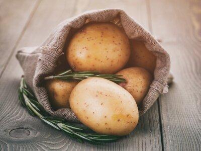 Quadro patate novelle in sacco del sacchetto con rosmarino sul tavolo di legno, annata tonica