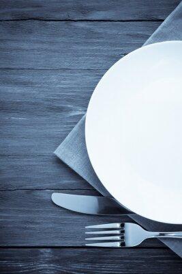 Quadro piatto bianco, coltello e forchetta su legno
