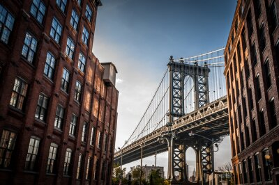 Quadro Ponte di Manhattan visto da uno stretto vicolo racchiuso da due edifici di mattoni in una giornata di sole in estate