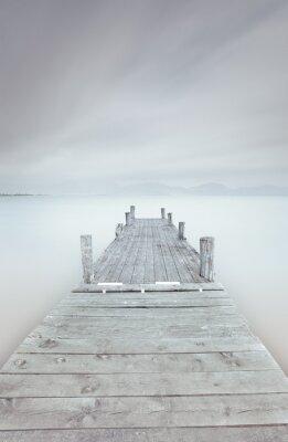 Quadro Pontile in legno sul lago in uno stato d'animo nuvoloso e nebbioso.