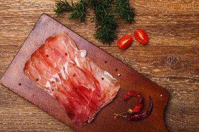Quadro prosciutto delizioso su una tavola di legno con le spezie.