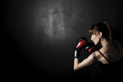 Quadro Pugile della donna con i guanti rossi su sfondo nero, alto contrasto con desaturato filtro grunge in studio