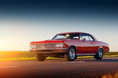 Quadro Retro soggiorno automobile rossa sulla strada asfaltata al tramonto