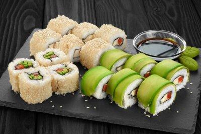 Quadro Rulli di sushi con avocado, salmone e semi di sesamo sul cassetto di ardesia.