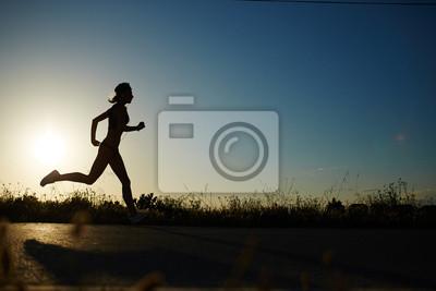 Quadro Silhouette di ragazza atletica correre lungo la strada per un tramonto