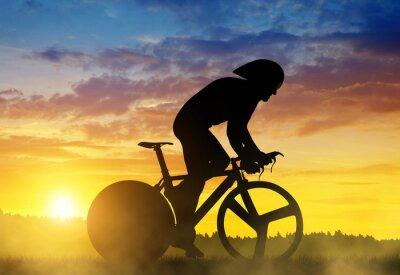 Quadro Siluetta di un ciclista su una bici da corsa della strada al tramonto.