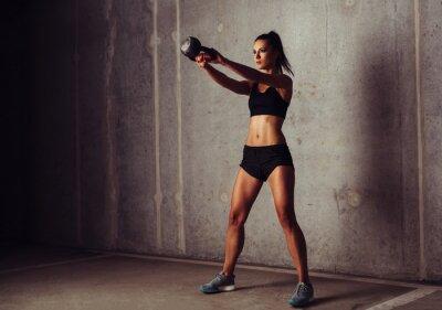 Quadro Slim sportiva attraente in un corso di formazione kettlebell