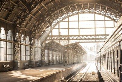 Quadro Stazione ferroviaria al tramonto alba in seppia. Carrello e piattaforma con tetto di costruzione. Viaggiare in treno in treno