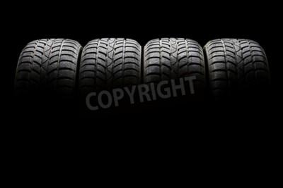 Quadro Studio shot di un set di quattro pneumatici per auto nero allineati orizzontalmente in un ambiente buio su sfondo nero