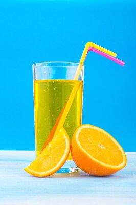 Quadro succo d'arancia in un bicchiere con cannucce colorate e fette d'arancia su sfondo blu